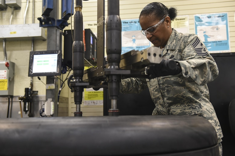 Chief Master Sgt. Shelina Frey, Air Mobility Command command chief, learns how to properly assemble a tire with the members of the 437th Maintenance Squadron Wheel and Tire shop in Joint Base Charleston, S.C., Nov. 17, 2017.