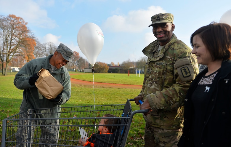 U.S. Air Force Chief Master Sgt. Jackie Harris, 24th Intelligence Squadron superintendent, left, loads a Thanksgiving package into a cart during an event sponsored by the United Services Organization on Vogelweh Military Complex, Germany, Nov. 18, 2017.  Senior enlisted leaders from multiple organizations in the Kaiserslautern Military Community teamed up with the USO to provide military members, pay grade E-5 and below, with Thanksgiving meals. (U.S. Air Force photo by Airman 1st Class Joshua Magbanua)