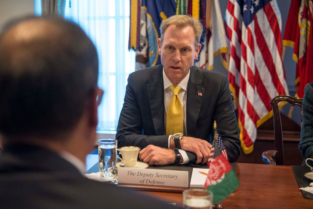 Deputy Defense Secretary Pat Shanahan sits at a table across from the acting Afghan defense minister.