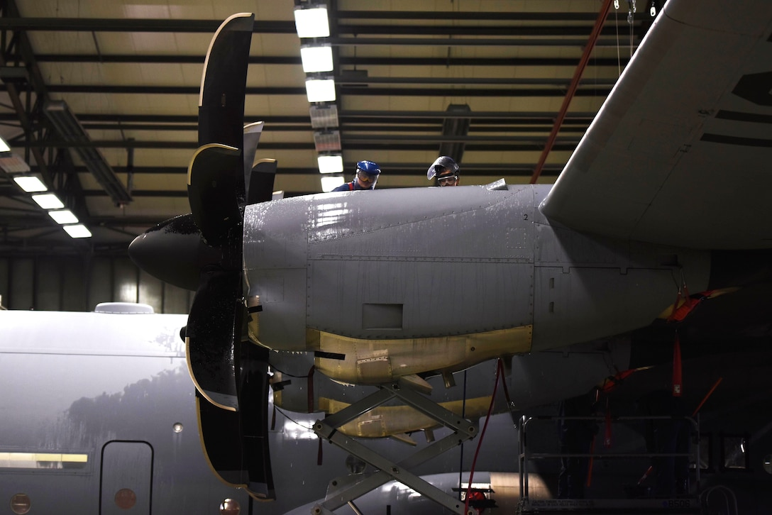 U.S. Air Force Senior Airman Rachel Revels (left), and U.S. Air Force Staff Sgt. Lindsay Hallford, both C-130J Super Hercules crew chiefs, spray a C-130J engine with cleaning solution on Ramstein Air Base, Germany, Nov. 20, 2017. Airmen clean the entirety of the aircraft before every inspection. (U.S. Air Force photo by Airman 1st Class Devin M. Rumbaugh)