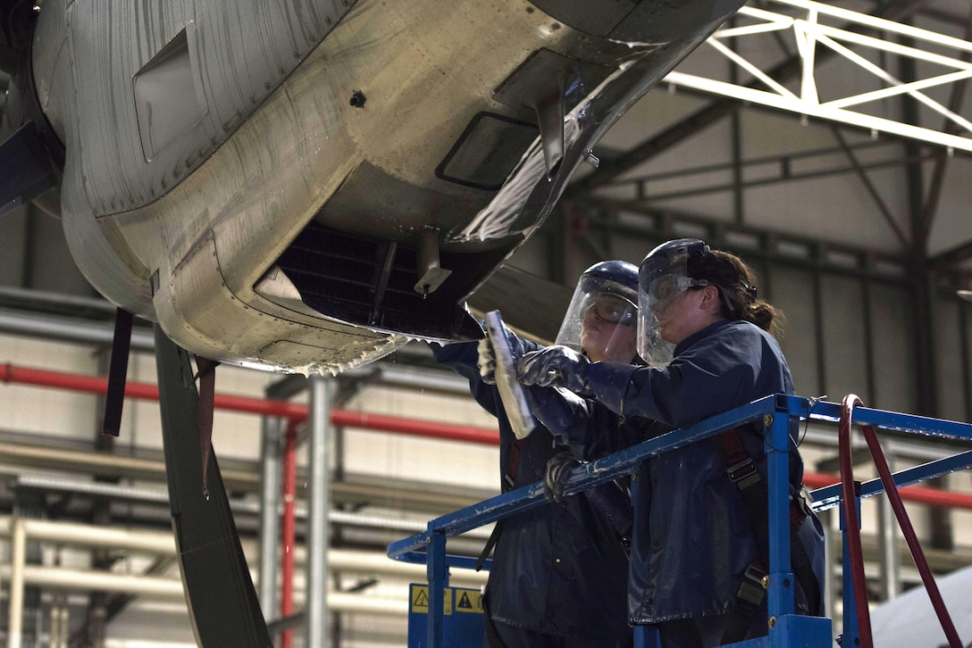 U.S. Air Force Senior Airman Rachel Revels (left), and U.S. Air Force Staff Sgt. Lindsay Hallford, both C-130J Super Hercules crew chiefs, scrub the grime off of a C-130J engine on Ramstein Air Base, Germany, Nov. 20, 2017. Airmen scrub the exterior of the aircraft with a cleaning solution repeatedly, then spray it with hot water to ensure it is clean. (U.S. Air Force photo by Airman 1st Class Devin M. Rumbaugh)