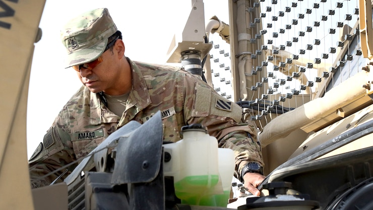 A person looks at the engine of a military vehicle.