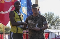 Commandant of the Marine Corps Gen. Robert B. Neller, right, presents a trophy to Denzel Ramirez, first place male finisher of the 9th Marine Corps Marathon (MCM) 10K, Arlington, Va., Oct. 22, 2017. Neller awarded trophies to the top three male and female finishers of the MCM and the MCM 10K.