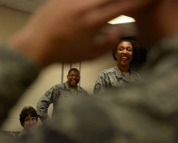 U.S Air Force Master Sgt. Shanique Rosario, 100th Air Refueling Wing Equal Opportunity office director, laughs during a discussion explaining the colors of the Four Lenses training exercise at RAF Mildenhall, England, Oct. 24, 2017. The training helps bring teams together by creating a basic understanding of each other's personality traits. The Equal Opportunity office offers training and resolution skills to active-duty members as well as civilians. (U.S. Air Force photo by Airman 1st Class Alexandria Lee)