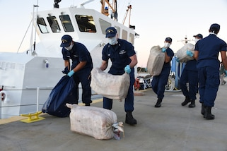 Crewmembers from the Coast Guard Cutter Pelican offload approximately one ton of cocaine
