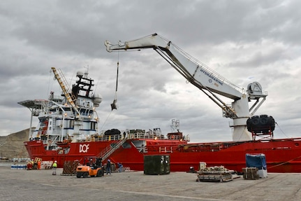 U.S. Sailors and Argentines load submarine rescue equipment onto a Norwegian construction support vessel