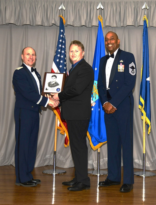Brig. Gen. Carl Schaefer, 412th Test Wing commander, and Chief Master Sgt. Roosevelt Jones, 412th Test Wing command chief, present Robert Topp, a maintenance mechanic with the 412th Civil Engineer Group, the John L. Levitow Award at the Airman Leadership School graduation ceremony for class 18A. Topp was the first civilian to earn the Levitow award. (U.S. Air Force photo by Christopher Ball)