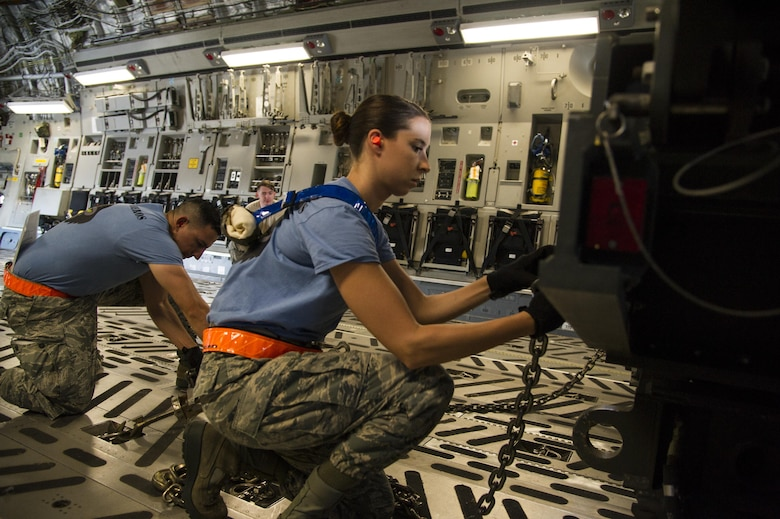 Tech. Sgt. Omar Morales and Staff Sgt. Kaitlyn Hilton, from the 735th Air Mobility Squadron, secure a vehicle during the aircraft loading competition during the Hickam Port Dawg Challenge, at Joint Base Pearl Harbor-Hickam, Hawaii, Nov. 17, 2017. The aerial port community hosts a Port Dawg Challenge every year to promote professionalism, and demonstrate air and space expeditionary force capabilities. (U.S. Air Force photo by Tech. Sgt. Heather Redman)