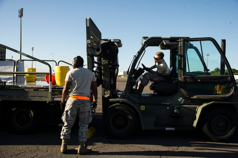 Staff Sgt. Pernell Hart, 735th Air Mobility Squadron assistance shift supervisor, guides Senior Airman Ron Motz, air freight journeyman, through the second leg of the forklift obstacle during the Hickam Port Dawg Challenge, at Joint Base Pearl Harbor-Hickam, Hawaii, Nov. 17, 2017. The aerial port community hosts a Port Dawg Challenge every year to promote professionalism, and demonstrate air and space expeditionary force capabilities. (U.S. Air Force photo by Tech. Sgt. Heather Redman)
