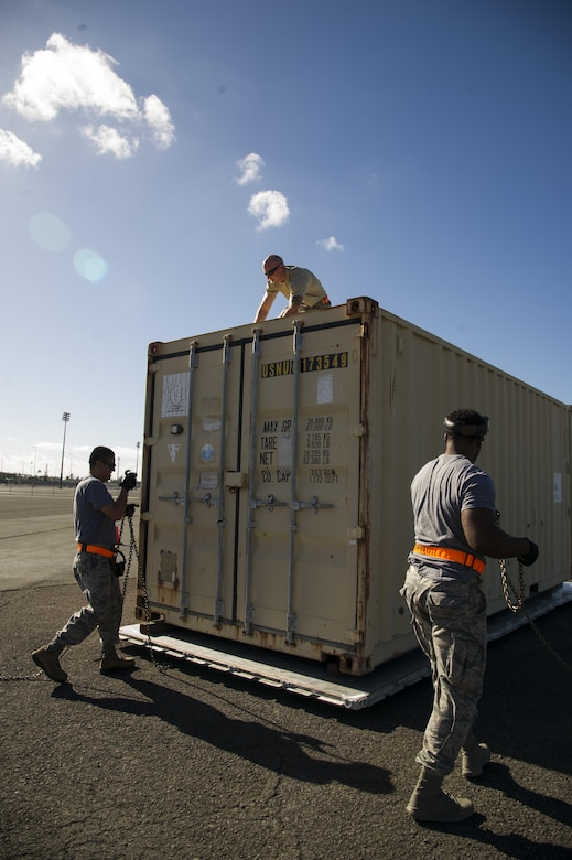 Tech. Sgt. Daniel Arrez, Staff Sgt. Nicholas Worrell, and Staff Sgt. Byron Patrick, from the 735th Air Mobility Squadron, secure a shipping container for the pallet build-up competition during the Hickam Port Dawg Challenge, at Joint Base Pearl Harbor-Hickam, Hawaii, Nov. 17, 2017. The aerial port community hosts a Port Dawg Challenge every year to promote professionalism, and demonstrate air and space expeditionary force capabilities. (U.S. Air Force photo by Tech. Sgt. Heather Redman)