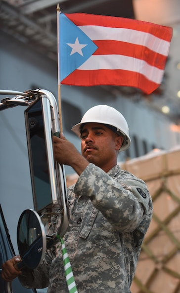U.S. Army Staff Sgt. Eliezer Casas, 690th Rapid Port Opening Element, 832nd Transportation Battalion, 597th Trans. Brigade distribution yard NCO in charge, fixes a Puerto Rico flag on a vehicle at Port of Ponce, Puerto Rico, Nov. 7, 2017.