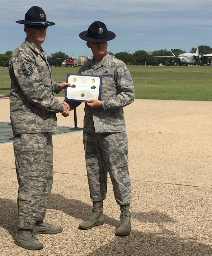 """Master Sgt. Joseph Dole (left), 331st Training Squadron, Joint Base San Antonio-Lackland, Texas, Blue Rope Association president, presents Master Sgt. Jason Wagner, 433rd Training Squadron, with a certificate recognizing his acceptance into the Master Military Instructor """"Blue Rope"""" Association. (Air Force photo)"""