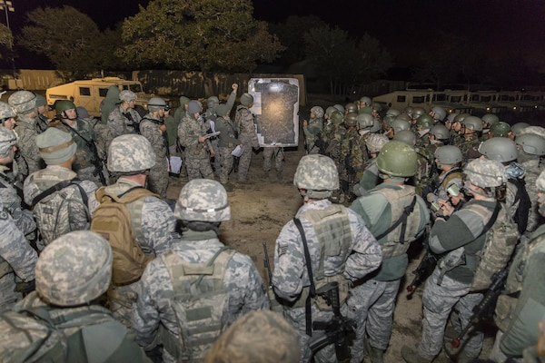 Students from the Inter-American Air Force Academy's 837th Training Squadron and 343rd TRS attend a pre-mission briefing at Joint Base San Antonio-Camp Bullis as part of their final training exercise Nov. 8, 2017. The students practiced reconnaissance, ambush, searching, and patrolling tactics. This was the first time the 837th TRS and 343rd TRS partnered for joint training.