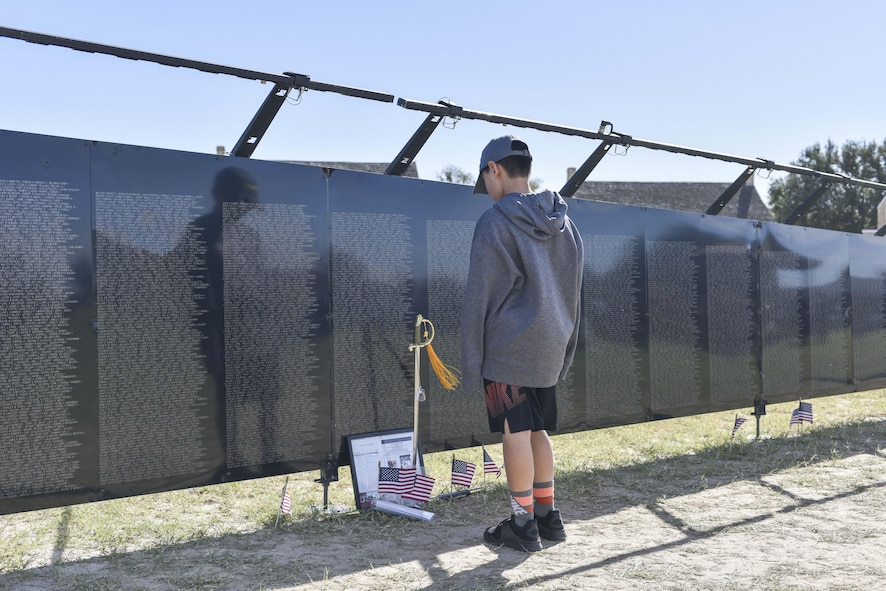 A child studies The Wall That Heals, a half-scale replica of the Vietnam War memorial, during the 50th Vietnam War Commemoration at the Fort Concho parade ground in San Angelo, Texas, Nov. 18, 2017.  The wall is approximately 250 feet in length, constructed of powder-coated aluminum, supported by an aluminum frame, and is made up of 24 individual panels. (U.S. photo by Airman 1st Class Randall Moose/released)