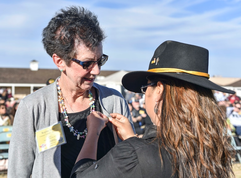 U.S. Air Force retired Col. Regina Aune receives a Vietnam veteran lapel pin from Aryn Lockhart, 17th Training Wing Public Affairs visual information specialist, during the 50th Vietnam War Commemoration at the Fort Concho parade ground in San Angelo, Texas, Nov. 18, 2017. Lockhart and Aune were both part of the humanitarian mission to evacuate orphans to their adoptive families known as Operation Babylift (U.S. photo by Airman 1st Class Randall Moose/released)