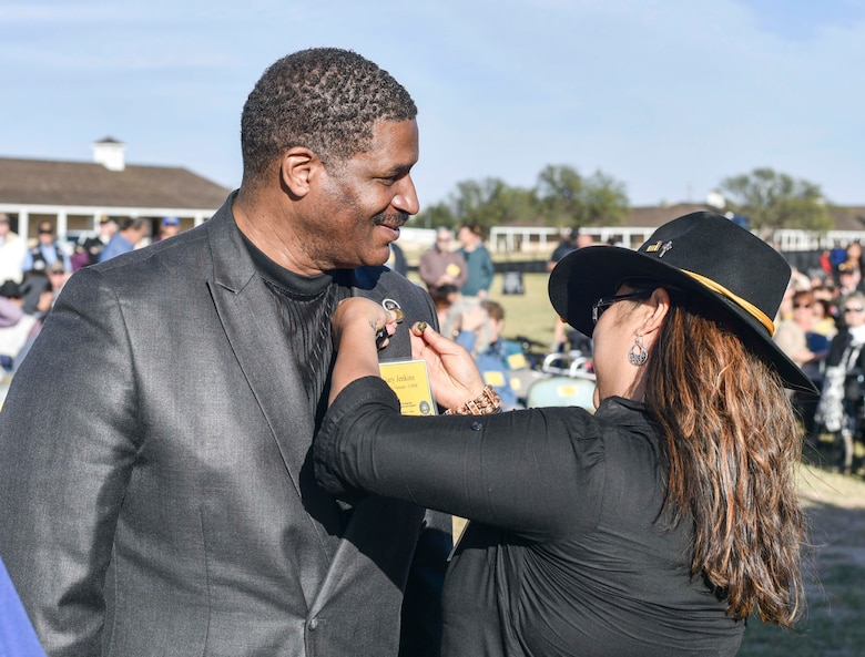 Gary Jenkins, 17th Training Wing Public Affairs audio visual production specialist, receives a Vietnam veteran lapel pin from Aryn Lockhart, 17TRW/PA visual information specialist, during the 50th Vietnam War Commemoration at the Fort Concho parade ground in San Angelo, Texas, Nov. 18, 2017.  The purpose of the pin is to recognize, thank and honor United States military veterans who served during the Vietnam War. (U.S. photo by Airman 1st Class Randall Moose/released)