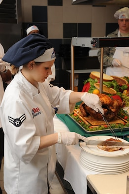 A female food service worker in white jacket and blue chefs hat, cuts turkey on a plate.