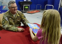 Lt. Gen. Brad Webb, commander of Air Force Special Operations Command, hands a book to one child.