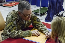 Lt. Gen. Brad Webb, commander of Air Force Special Operations Command, signs a copy of a book for one child.