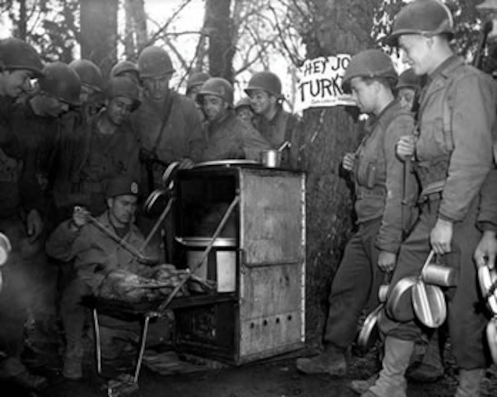 A male U.S. Army Sergeant prepares two Thanksgiving turkeys on a camp stove for his fellow male soldiers who surround him out in the woods.