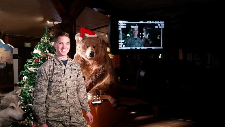 Senior Airman Jared Bunn, 673d Air Base Wing Public Affairs broadcaster, checks his camera gear during last year's holiday greetings event at Joint Base Elmendorf-Richardson, Alaska. Holiday greetings are a way for service members to send a message to their families back home if they can't make it themselves.