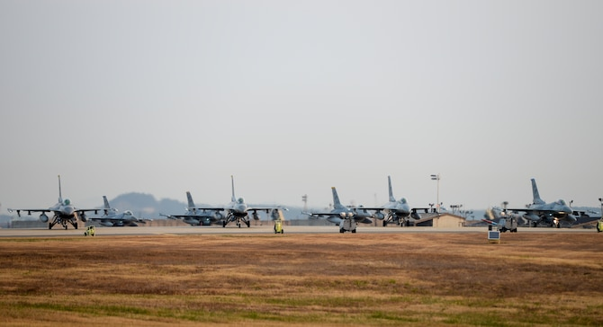 U.S. Air Force F-16 Fighting Falcons from the 80th and 35th Fighter Squadrons under the 8th Fighter Wing await take-off clearance at the end of the runway at Kunsan Air Base, Republic of Korea, Nov. 17, 2017. The 8th FW conducted what's known as a large force employment to test the wing's ability to generate numerous aircraft in support of combat training sorties. (U.S. Air Force photo by Capt. Christopher Mesnard)