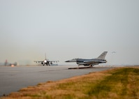 A U.S. Air Force F-16 Fighting Falcon with the 80th Fighter Squadron uses its afterburner to take off at Kunsan Air Base, Republic of Korea, Nov. 17, 2017, while a pilot with the 35th FS taxis to take off behind. The two fighter squadrons carry out a wide variety of combat sorties in support of contingency operation plans on the Korean Peninsula. These aircraft took part in a large force employment involving more than 20 aircraft to test their ability to conduct such missions. (U.S. Air Force photo by Capt. Christopher Mesnard)