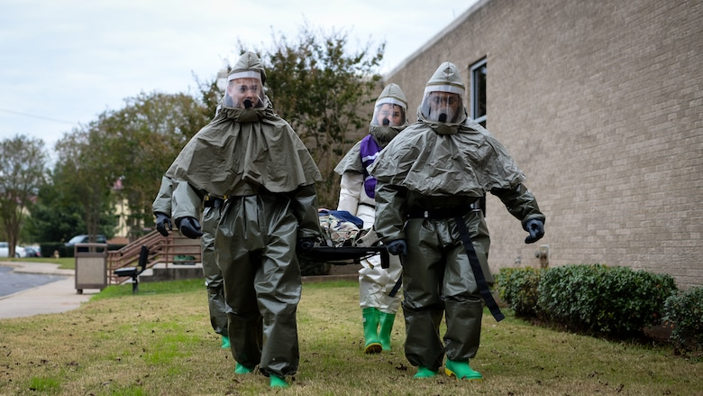 Decontamination team members from the 2d Medical Group carry a simulated chemical attack victim on a litter during a decontamination exercise on Barksdale Air Force Base, La., Nov. 15, 2017. Home station medical response includes decontamination, triage and a security team which uses the PAPR, a power air purified respirator suit which provides protection against CBRN agents. (U.S. Air Force photo by Staff Sgt. Benjamin Raughton)