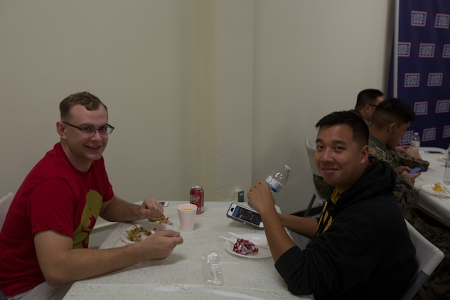 CAMP FOSTER, OKINAWA, Japan – Lance Cpl. Eric Peterson, left, and Cpl. Christopher Hoang pose for a photo during the USO Thanksgiving Dinner Nov. 21 at the USO aboard Camp Foster, Okinawa, Japan.
