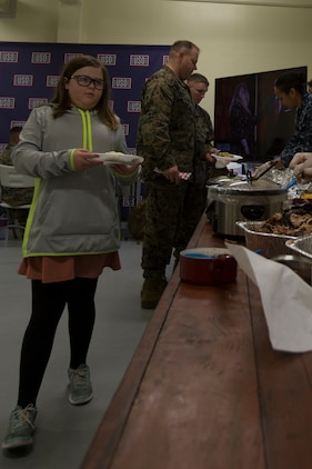 CAMP FOSTER, OKINAWA, Japan – A child gets food at the USO Thanksgiving Dinner Nov. 21 at the USO aboard Camp Foster, Okinawa, Japan.