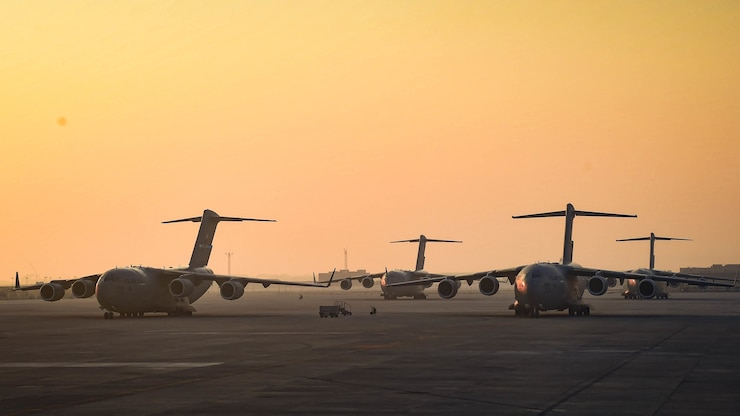 Military planes sit on a flight line with an orange sky in the background.