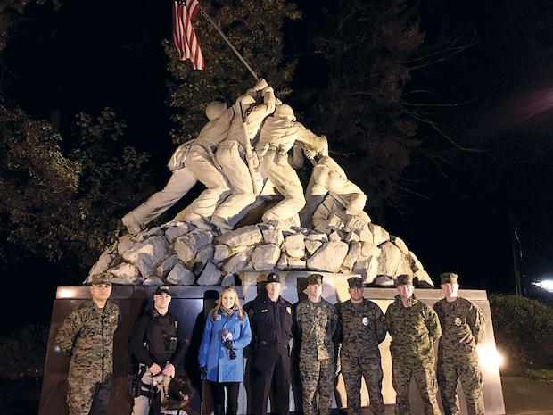 """WJLA ABC Channel 7 reporter Eileen Whelan (center) stands with members of the Provost Marshal Office at the Quantico Iwo Jima statue at the front gate entrance to the base.  She was here Nov. 8 as part of WJLA's """"Thank you for your service"""" series highlighting the military in the region.  For the full story see page 8."""