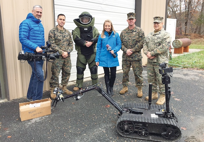 om left to right: Mike Rudd, WJLA, SSgt Alfredo Andrade, Explosive Ordinance Disposal (EOD) technician, Sgt. Wesley Buzzard EOD technician, Eileen Whelan, WJLA, Maj. A.J. Bormann director, Quantico office of Communication, and Master Gunnery Sgt. David Alexander EOD chief, demonstrate how they approach suspicious packages