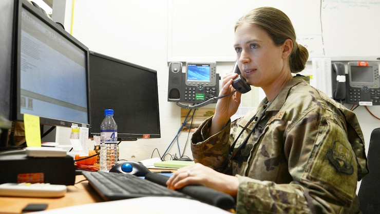 An airman sitting at a desk talks on the phone.