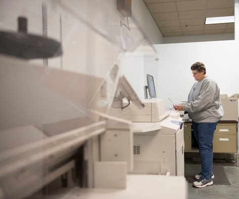 Photo of Teresa Blake, Documentation Automation Printing Services electronic duplicating system operator, inspecting a print job at Mountain Home Air Force Base, Idaho, Nov. 16, 2017.