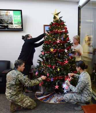 Air Force Special Operations Command members (four people) place stars on a Christmas tree