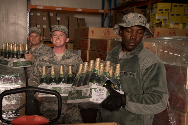 Airmen from the 386th Expeditionary Force Support Squadron carry sparkling grape juice through a storeroom Dec. 22, 2016 at an undisclosed location in Southwest Asia. These Airmen were assembling tri-walls of holiday meal items for forward-deployed service members (U.S. Air Force photo/Staff Sgt. Andrew Park)