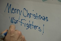 Chief Master Sgt. James Lucas, 386th Expeditionary Mission Support Group superintendent, writes a holiday greeting on the top of a box containing holiday meals for forward-deployed service members Dec. 23, 2016 at an undisclosed location in Southwest Asia. After the boxes were loaded with holiday meal items, they were loaded into the back of a C-130H Hercules and delivered to the austere locations where these service members are currently deployed. (U.S. Air Force photo/Staff Sgt. Andrew Park)