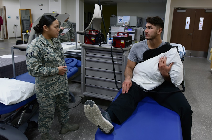 U.S. Air Force Senior Airman Tiffani-Amber Petit, left, a physical therapy technician assigned to the 509th Medical Operations Squadron, discusses post-shoulder surgery treatment with Senior Airman Moses Debraska, a security response member assigned to the 509th Security Forces Squadron, at Whiteman Air Force Base, Mo., Nov. 15, 2017.