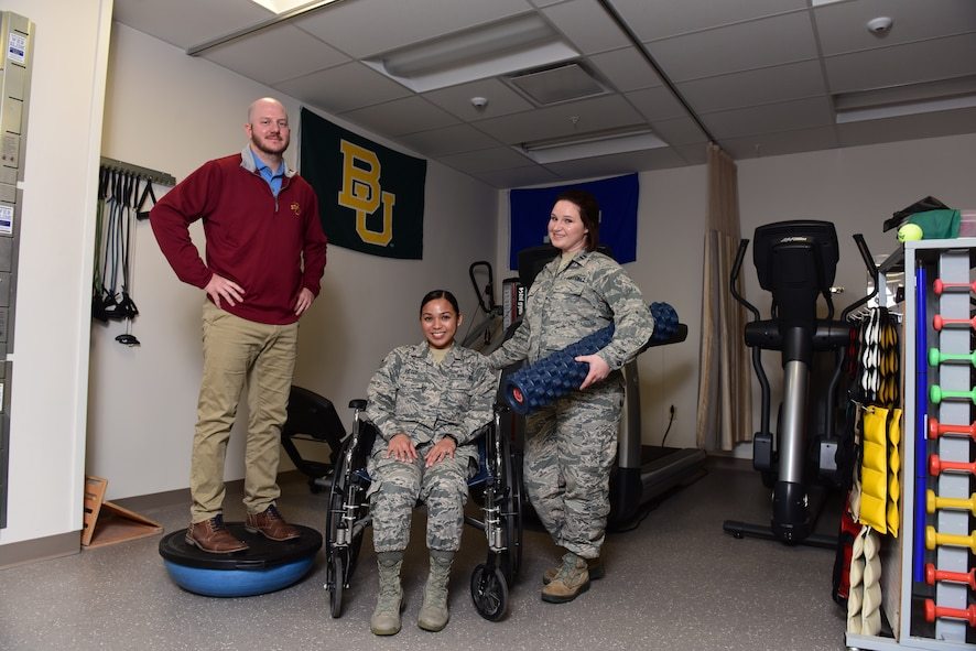 From left to right, U.S. Air Force Senior Airman Tiffani-Amber Petit, a physical therapy technician, Chris Buhr, a physical therapy assistant, and Capt. Bridgette Griffiths, the physical therapy element chief, all assigned to the 509th Medical Operations Squadron, pose with various physical therapy equipment at Whiteman Air Force Base, Mo., Nov. 20, 2017.