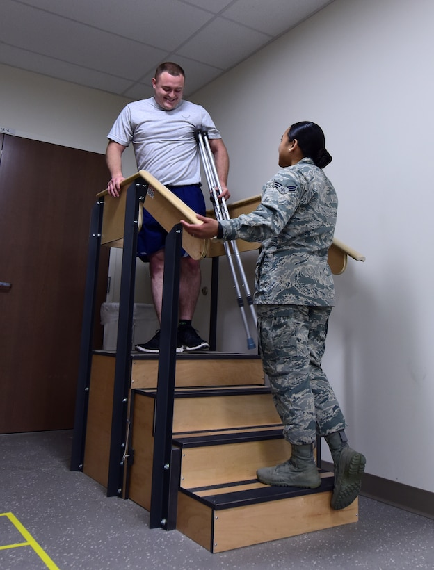 U.S. Air Force Staff Sgt. Brandon Berry, an electrical power production specialist assigned to the 509th Civil Engineer Squadron, is trained by Senior Airman Tiffani-Amber Petit, a physical therapy technician assigned to the 509th Medical Operations Squadron, on how to use crutches when traveling down a stair case to avoid further injury at Whiteman Air Force Base, Mo., Nov. 15, 2017.