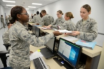 Airman 1st Class Maiesha Buford, 72nd Aerospace Medicine Squadron, gives Capt. Theresa Hall, 72nd Medical Support Squadron, her mobility papers after they were checked for current shot records, public health, mental health, malaria medication, and biological warfare/chemical warfare kits Oct. 4, 2017, Tinker Air Force Base, Oklahoma.