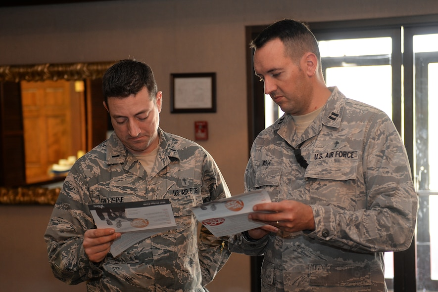 Chaplain (1st Lt.) John Gillispie, 55th Wing Chapel and Chaplain (Capt.) Robert Rose look through the list of charities for the 2017 Combined Federal Campaign at the CFC kick-off on Nov. 21, 2017 at the Patriot Club on Offutt AFB, Neb.