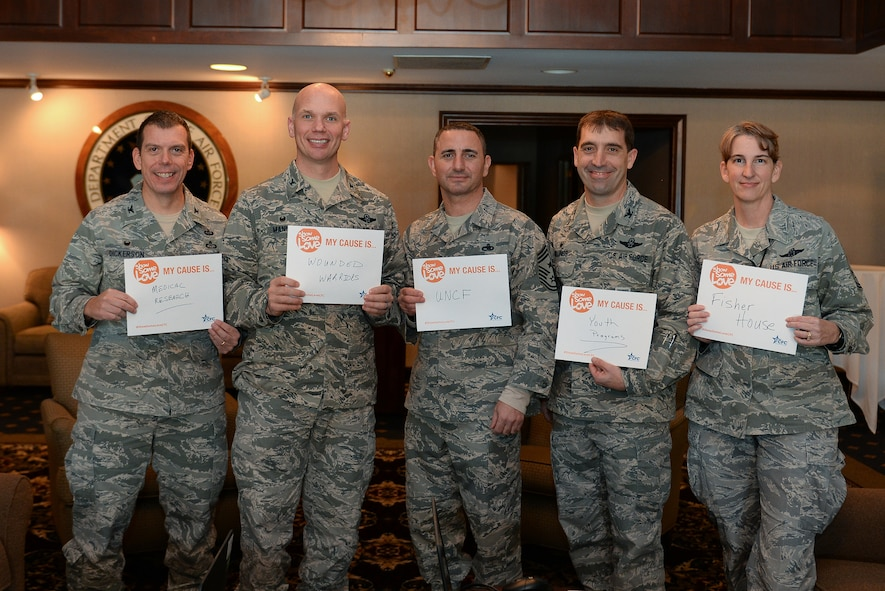 (L to R) Col. Steven Dickerson, 557th Weather Wing commander, Col. Michael Manion, 55th Wing commander and Chief Master Sgt. Brian Kruzelnick, 55th Wing command chief, Col. Robert Billings, 595th Command and Control Group commander and Chief Master Sgt. Margaret Haldie, 595th Command and Control Group command chief show signs displaying their choice of charitable organizations after signing up at the kick-off of the 2017 Combined Federal Campaign on Nov. 21, 2017 at the Patriot Club on Offutt AFB, Neb.