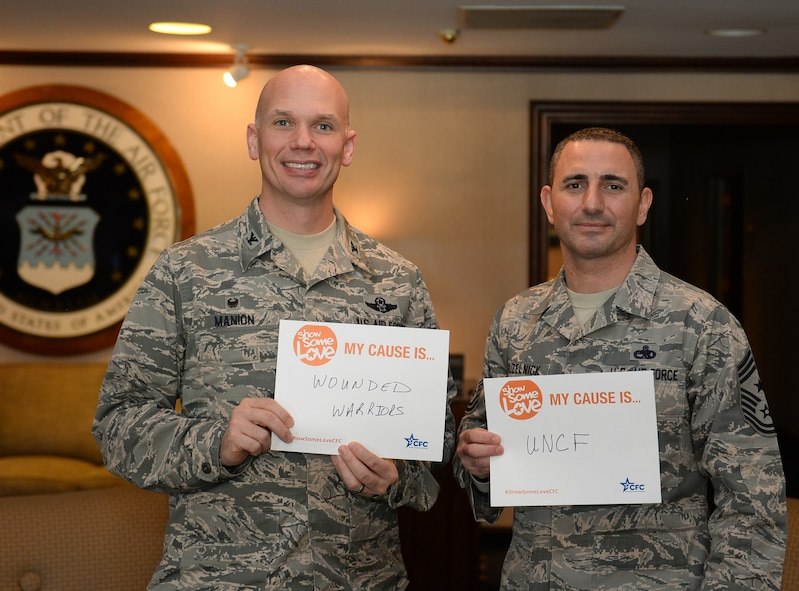 Col. Michael Manion, 55th Wing commander and Chief Master Sgt. Brian Kruzelnick, 55th Wing command chief show signs displaying their choice of charitable organizations after signing up at the kick-off of the 2017 Combined Federal Campaign on Nov. 21, 2017 at the Patriot Club on Offutt AFB, Neb.