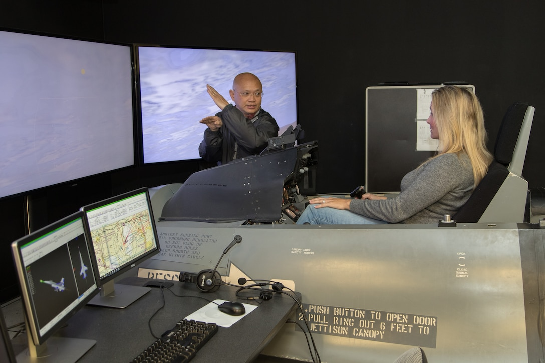 """Aaron Fong, 412th Electronic Warfare Group, briefs Michelle West on her """"mission"""" in the flight simulator during an Honorary Commanders' event at the Integrated Facility for Flight Avionics Systems Testing. (U.S. Air Force photo by Don Allen)"""