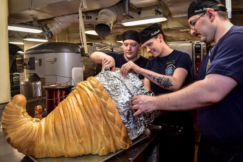 Three sailors make a cornucopia for Thanksgiving dinner.