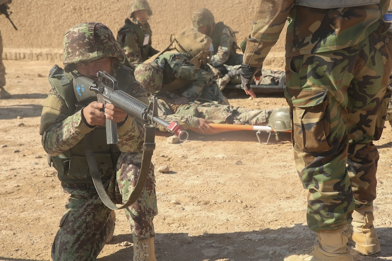 An Afghan National Army soldier with 6th Kandak, 1st Brigade, 215th Corps holds security as two notionally wounded soldiers receive medical care during casualty evacuation training at Camp Shorabak, Afghanistan, Nov. 19, 2017. The Helmand Regional Military Training Center implemented its first iteration of CASEVAC training using Afghan air assets as part of the operational readiness cycle to help prepare its students for real-world missions. U.S. advisors assigned to various train, advise, assist commands from throughout Afghanistan observed the training in preparation for integrating standardized CASEVAC rehearsals into their unit's ORCs. (U.S. Marine Corps photo by Sgt. Lucas Hopkins)