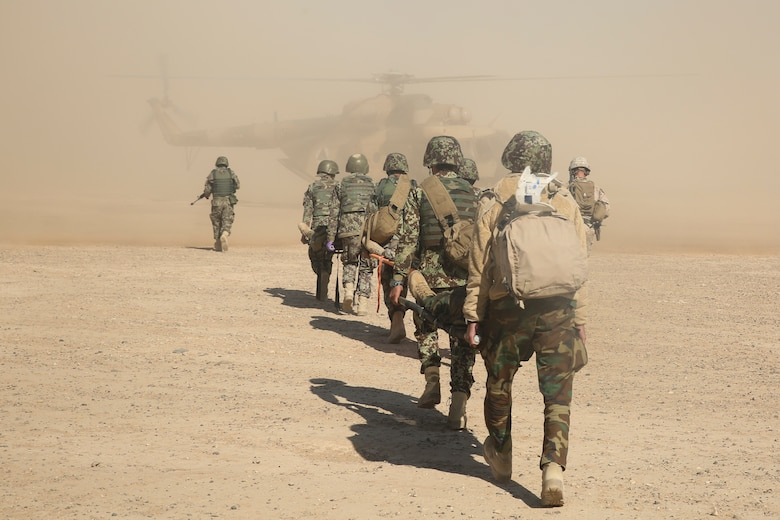 Afghan National Army soldiers with 6th Kandak, 1st Brigade, 215th Corps carry notionally wounded soldiers toward an Mi-17 helicopter during casualty evacuation training at Camp Shorabak, Afghanistan, Nov. 19, 2017. As part of the operational readiness cycle, Afghan instructors at the Helmand Regional Military Training Center held the first iteration of CASEVAC training during the two-month course to help prepare its students for operations against the Taliban. U.S. advisors assigned to multiple train, advise, assist commands from throughout Afghanistan observed the simulation to implement standardized CASEVAC training into their respective RMTCs training cycles. (U.S. Marine Corps photo by Sgt. Lucas Hopkins)