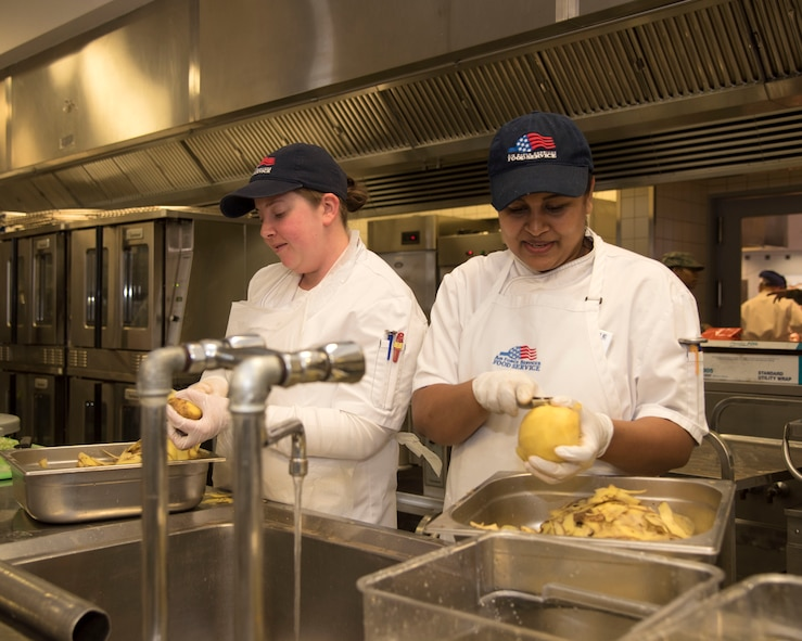 Nicole Kuhn (left) and Nuwanthi Angel, 786th Force Support Squadron cook helpers, prepare food during the Thanksgiving meal at Ramstein Air Base, Germany, Nov. 23, 2017.